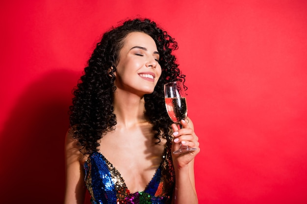 Крупным планом портрет великолепной веселой мечтательной волнистой девушки, пьющей вино, наслаждаясь отдыхом, изолированным на ярко-красном цветном фоне