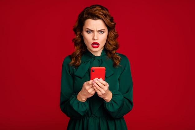 Крупным планом портрет великолепной девушки, использующей ячейку, изолированную на фоне красного цвета