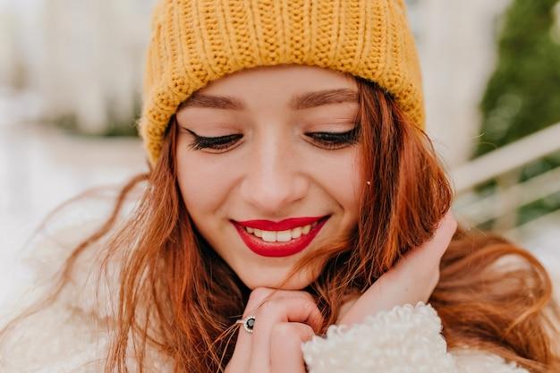 赤い唇を持つゴージャスな女の子のクローズアップの肖像画。冬にポーズをとって帽子をかぶった恥ずかしがり屋の生姜の女性。