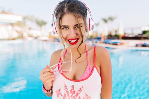 Крупным планом портрет великолепной девушки с загорелой кожей, держащей солнцезащитные очки и милой улыбкой, наслаждающейся отдыхом в отпуске