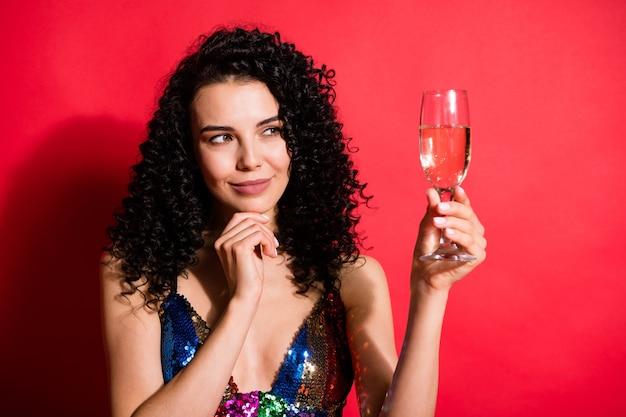 Крупным планом портрет великолепной довольно веселой волнистой девушки, пьющей вино, думая о желании, мечте, изолированной на ярко-красном цветном фоне