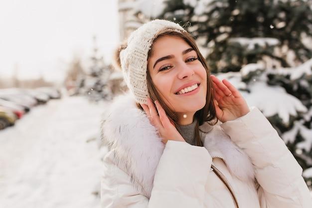 雪の降る冬の日に路上でポーズ青い目を持つ豪華な女性のクローズアップの肖像画。笑ってニット帽子の魅力的な女性モデルの屋外写真
