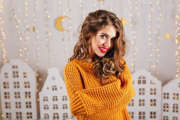 Портрет крупным планом сероглазой девушки с вьющимися волосами, позирующей в вязаном свитере на светлой стене с игрушечными домиками.