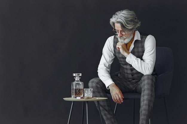 Закройте вверх по портрету усмехаясь старомодного человека. гентельман сидит на стуле. дедушка с бокалом виски.