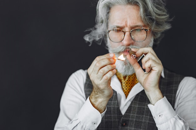Закройте вверх по портрету усмехаясь старомодного человека. дедушка с сигарой.
