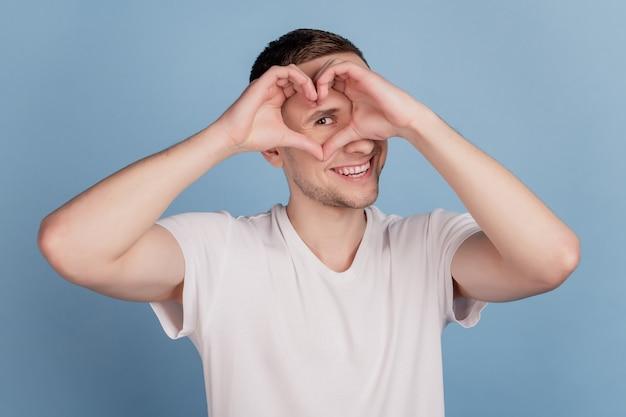 青い背景の上に孤立したハートサインバレンタインデールックアイを示す男の幸せな笑顔のクローズアップの肖像画
