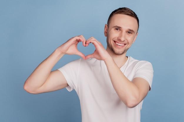 青い背景の上に分離されたハートサインバレンタインデーのロマンスを示す男の幸せな笑顔のクローズアップの肖像画