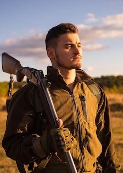 Hamdsome 헌터의 초상화를 닫습니다. 사냥에 샷건 총을 가진 사냥꾼. 사냥꾼은 숲에서 소총을 목표로합니다. 헌터 맨.