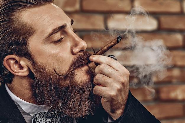 レンガの壁の背景に茶色の葉巻を吸っている口ひげとあごひげを持つハンサムな残忍な男の肖像画を閉じます。煙の概念