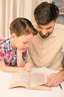 彼の息子に本を読んでハンサムな父の肖像画をクローズアップ