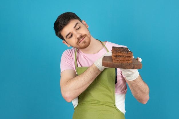 /チョコレートケーキのスライスを保持しているハンサムな男の肖像画を閉じます。