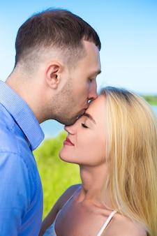 彼のガールフレンドにキスするハンサムな男の肖像画をクローズアップ