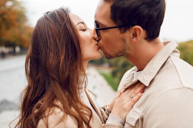 彼の妻が外を抱いてハンサムな男の肖像画を閉じます。ロマンチックな瞬間。