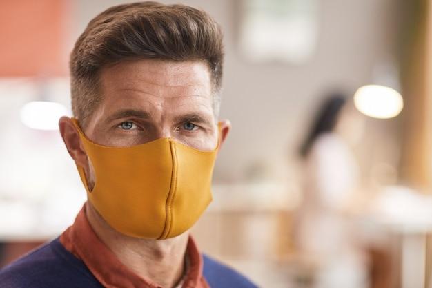 마스크를 쓰고 사무실 인테리어에 서있는 동안 카메라를보고 잘 생긴 성숙한 남자의 초상화를 닫습니다, 복사 공간