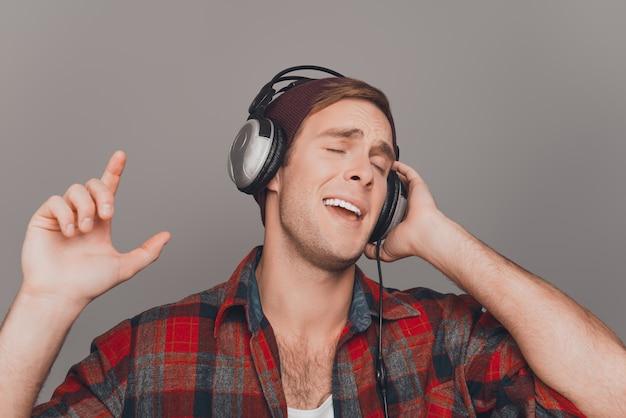 음악을 듣고 헤드폰에 잘 생긴 음악 팬의 초상화를 닫습니다
