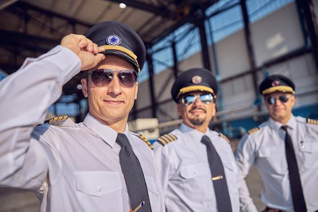 Крупным планом портрет красивого пилота в белой форме, держащего руку на шляпе, стоя перед двумя другими пилотами в солнечных очках