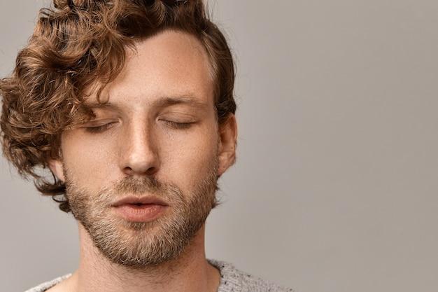 スタイリッシュな髪型とそばかすのあるハンサムな無精ひげを生やした若い男性の肖像画をクローズアップし、目を閉じて穏やかな穏やかな表情を持ち、朝に瞑想を練習します。調和とバランス