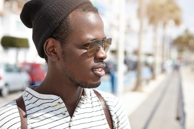 スタイリッシュな色合いと暑い晴れた朝に外国の街で素敵な散歩をして帽子をかぶったハンサムな若いアフリカ系アメリカ人男性学生のクローズアップの肖像画