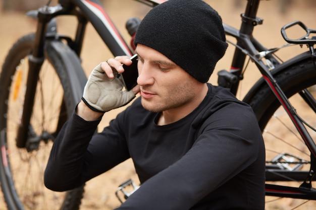 森での集中的なサイクリングトレーニングの後にリラックスしながら、黒いスポーツウェアと彼のガールフレンドや妻に携帯電話で話しているキャップを身に着けているハンサムな若いヨーロッパのバイカーの肖像画を閉じます。
