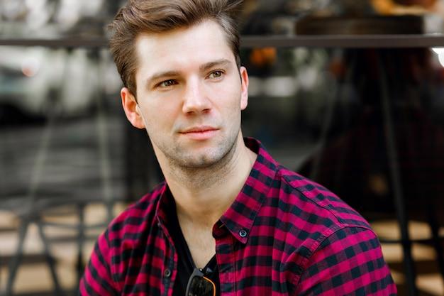Крупным планом портрет красивого молодого хипстера, карие глаза, в модной клетчатой рубашке, позирует возле городского кафе.