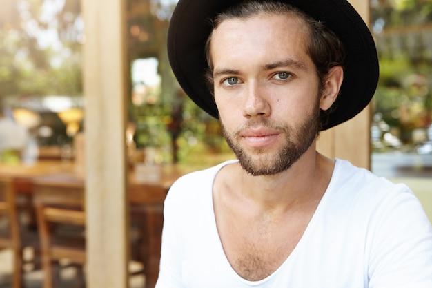 Крупным планом портрет красивый молодой битник с нечеткой бородой, одетый в черную шляпу и белую футболку, глядя со слабой улыбкой