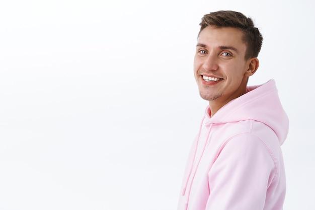 Крупным планом портрет красивого молодого студента со светлыми волосами, щетиной, стоящего в профиль и повернутого к камере с сияющей улыбкой, выглядящего довольным и счастливым, стоящая белая стена