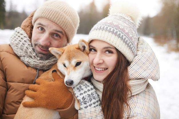 冬の森で一緒に屋外散歩を楽しみながらかわいい犬を保持し、カメラを見ている幸せな大人のカップルの肖像画をクローズアップ