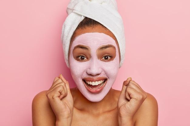 幸せなアフリカ系アメリカ人女性の肖像画をクローズアップは拳を食いしばり、バラ色の粘土マスクを適用し、スパ療法を受け、濡れた髪に包まれたタオルを着用します