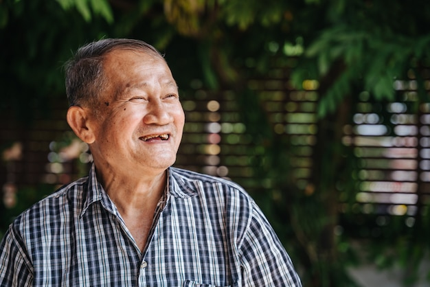 幸せなアジアの年配の男性のクローズアップの肖像画は、希望を持って見えます。老タイ人、健康なシニアコンセプト