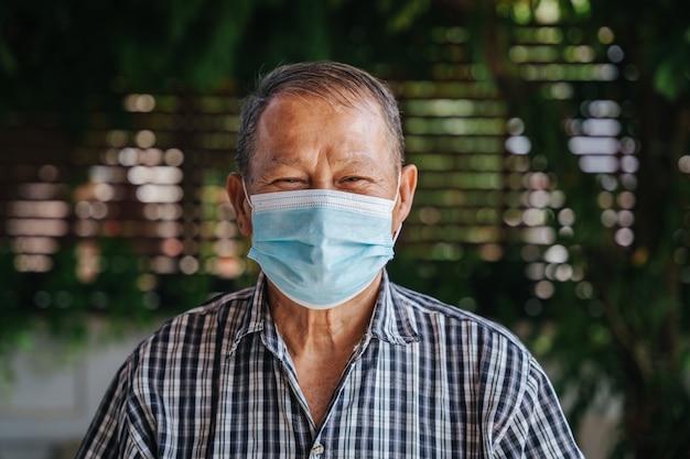 幸せなアジアの年配の男性のクローズアップの肖像画はマスクを着用します