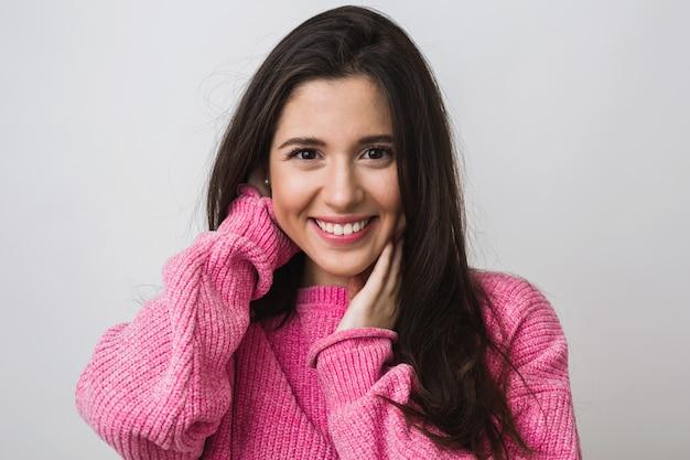 暖かいピンクのセーター、長い髪、自然な表情、誠実な笑顔、肯定的な気分、分離で幸せな魅力的な女性の肖像画を間近します。