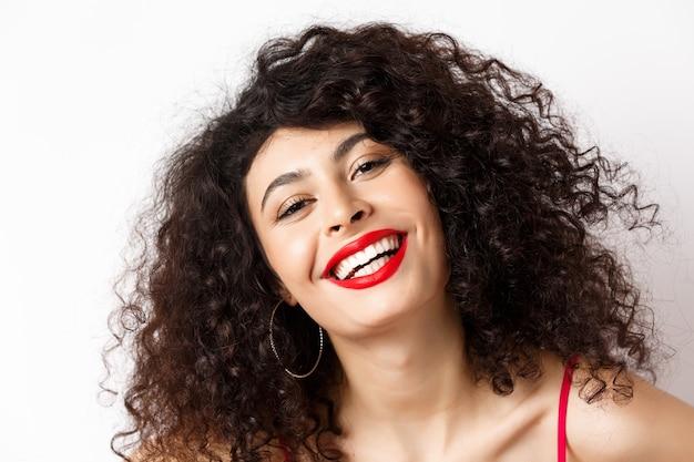 巻き毛と赤い唇、笑顔の白い歯を持つ幸せな美しい女性のクローズアップの肖像画は、幸せと喜びを表現します。