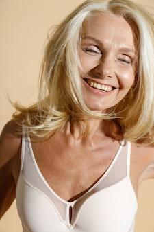 目を閉じて笑っている白いランジェリーで幸せな白人の成熟したブロンドの女性の肖像画をクローズアップ