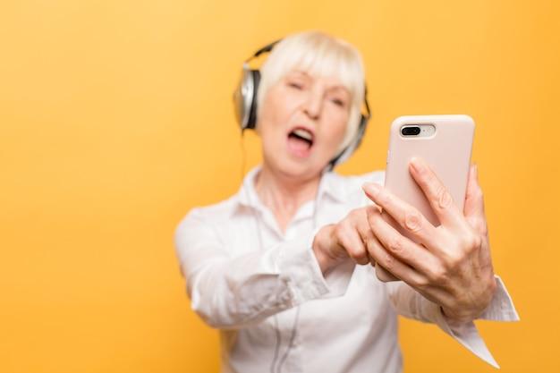 노란색 배경에 고립 된 인터넷을 통해 화상 통화를 데 이빨 전송 해 미소 할머니 할머니 할머니와 함께 행복 한 쾌활 한 흥분된 유쾌의 초상화를 닫습니다.