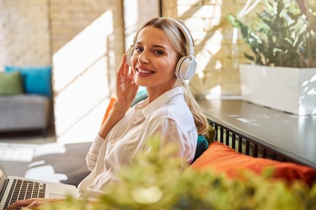 屋内の写真カメラで笑っているヘッドフォンで幸せな陽気な女性の肖像画をクローズアップ