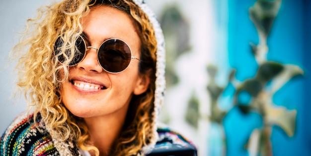 サークルサングラス幸せな女性を身に着けている幸せな陽気な若い大人の女性の肖像画をクローズアップ