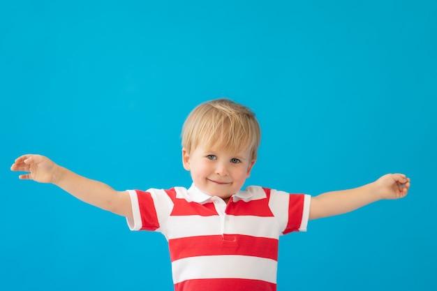青い壁に縞模様のシャツを着て幸せな子の肖像画を閉じます。