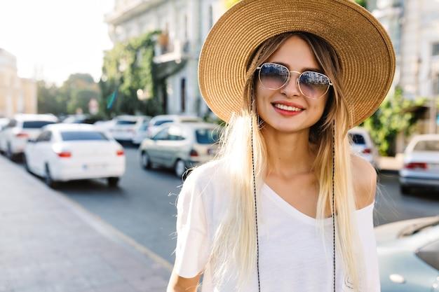 街の建物のそばで日光の下でファッションサングラスと帽子を身に着けている幸せな存在の女の子の肖像画をクローズアップ。自由奔放に生きるスタイルに身を包んだスタイルの女性が通りを歩く