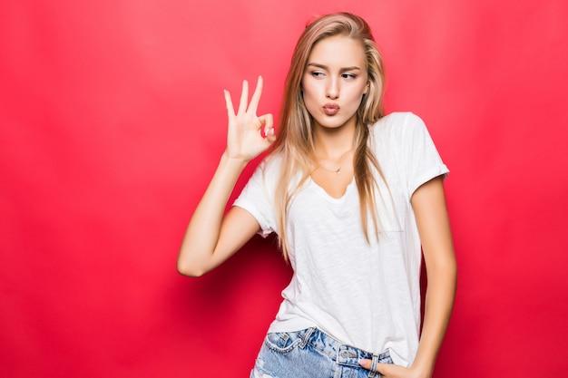 Крупным планом портрет счастливой девушки, жестикулирующей знак ок, изолированные на красном фоне