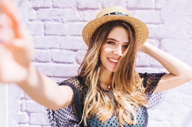 Крупным планом портрет счастливой девушки с волосами до середины спины, делающей селфи и держащей соломенную шляпу