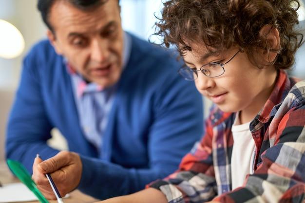 自宅の机に座って父親と一緒に宿題をしている幸せな小さなヒスパニック系の学校の男の子の肖像画を閉じます。オンライン学習、家族、父性の概念