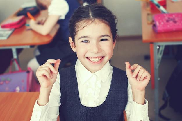 Крупным планом портрет счастливой маленькой школьницы