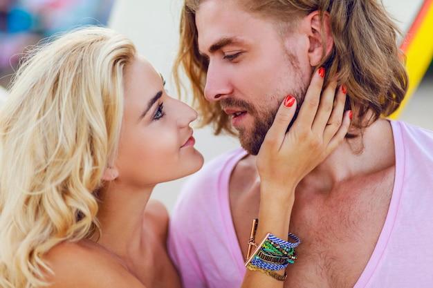 太陽が降り注ぐビーチで幸せな男と女の肖像画を閉じる