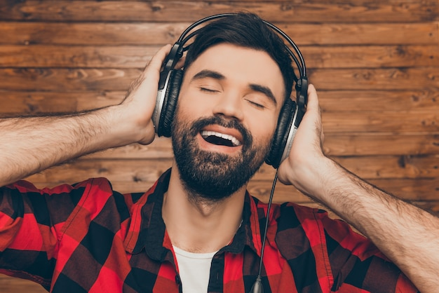 音楽を聴いて目を閉じて歌う幸せな男の肖像画をクローズアップ