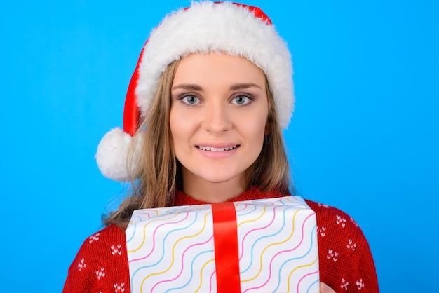 クリスマスの衣装で幸せな笑顔のかわいい素敵な優しい女性の肖像画をクローズアップは、明るい青色の背景で隔離のプレゼントボックスの後ろに隠れています