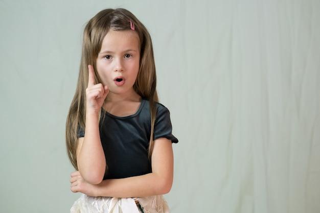 考えを持つ彼女の指を保持している長い髪の幸せな笑顔の少女のクローズアップの肖像画。