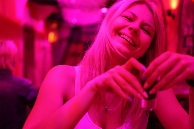 Крупным планом портрет счастливой улыбающейся женщины в баре или кафе с неоновыми огнями