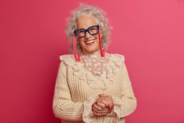 Крупным планом портрет счастливой морщинистой модной бабушки в очках и свитере