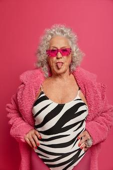 ピンクのタイツとコートを着て幸せなしわのファッショナブルなおばあちゃんの肖像画をクローズアップ