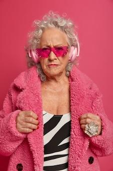 분홍색 스타킹과 코트를 입고 행복한 주름진 유행 할머니의 초상화를 닫습니다